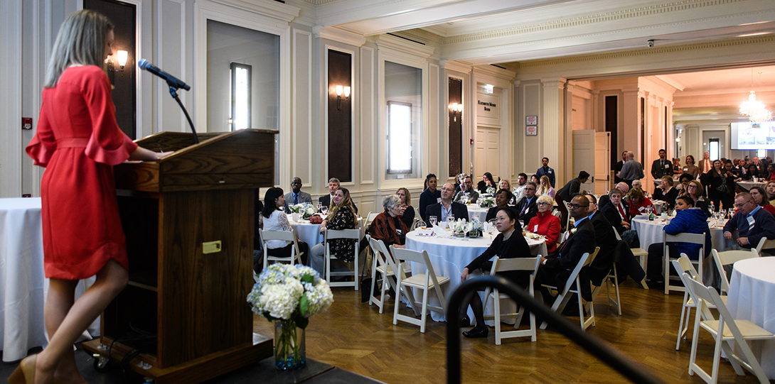 An alumni honoree delivers a speech at a podium looking out at event attendees seated at tables,, at the 2018 Annual Alumni Celebration.
