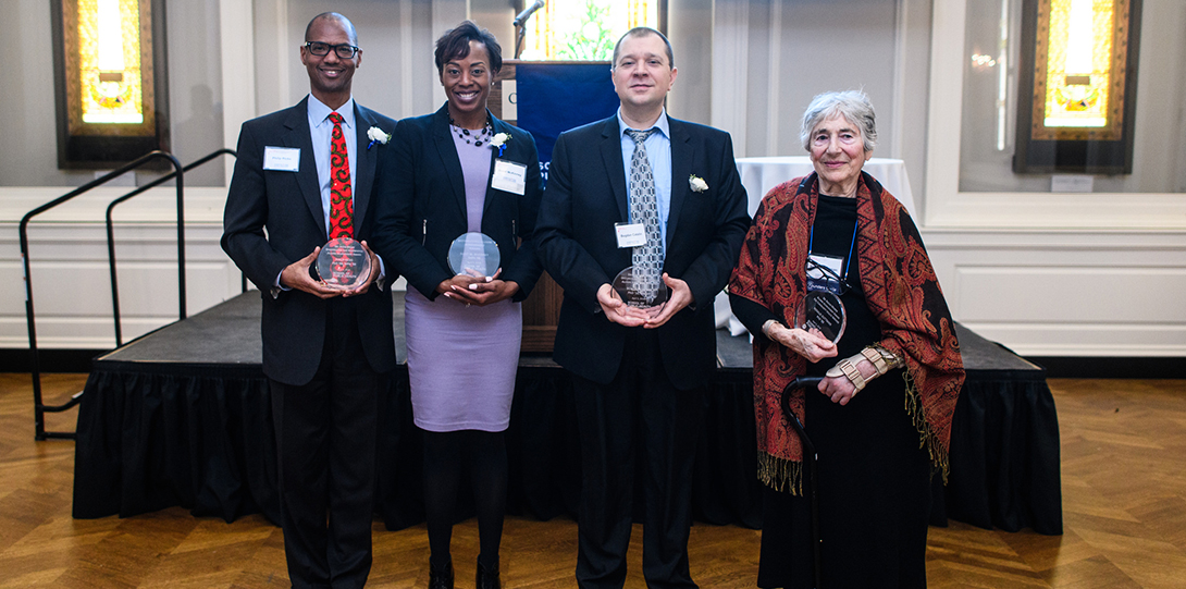 The 2018 alumni honorees pose with their glass plaques, while standing in front of the dias.