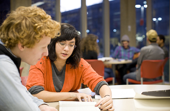 A female student sits with a male student, helping with him with his homework. The woman's hand is on the man's notebook, following a line of text as she reads.
