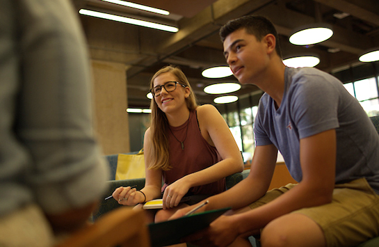 Two students are listening to a third student during a conversation, with one of the listening students taking notes on a pad of paper.