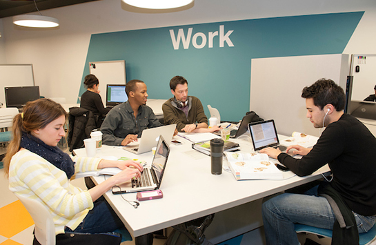 Students sit at a table at the C-Stop at UIC, a dedicated space for student studying and engagement.  These students are all seated with a laptop, typing on their laptops.