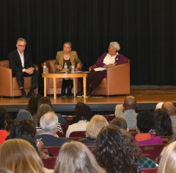 A scene from the Alumni Learning Series, with panelists sitting in chairs on the stage while audience members sit in chairs in the auditorium, listening to the discussion.