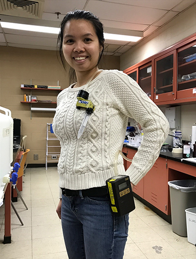 A student researchers poses for a photo wearing an electronic air sampler, which consists of a black power unit attached to her belt and a plastic air intake tube attached to her sweater.