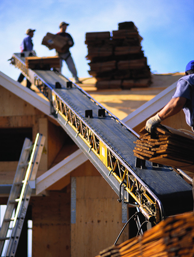 A construction worker sends a bundle of shingles up a conveyor belt toward a roof, where two workers are unloading the bundles of shingles and stacking them on the roof.