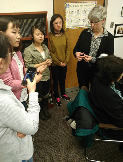 UIC professor Susan Buchanan stands with a group of Asian women, engaged in a question and answer session as part of the mercury research project.
