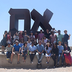 Sayuri Fujita poses for a photo with other fieldwork students in Israel, standing in front of a large sculpture of two Hebrew letters.