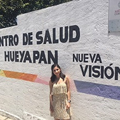 Celina Garza poses for a picture standing in front of a white brick wall during her field experience in Mexico.