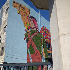 A building in Jordan painted with a large mural of a person in native Jordanian clothing walking next to a camel.