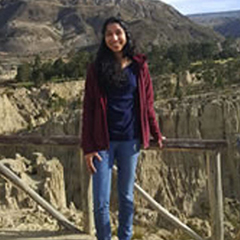 Meghna Nagam poses for a picture standing in front of a series of mountains in the background.