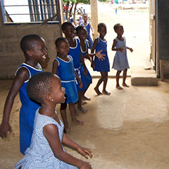 A group of children perform a dance with Mary Otoo, who is not included in the picture.