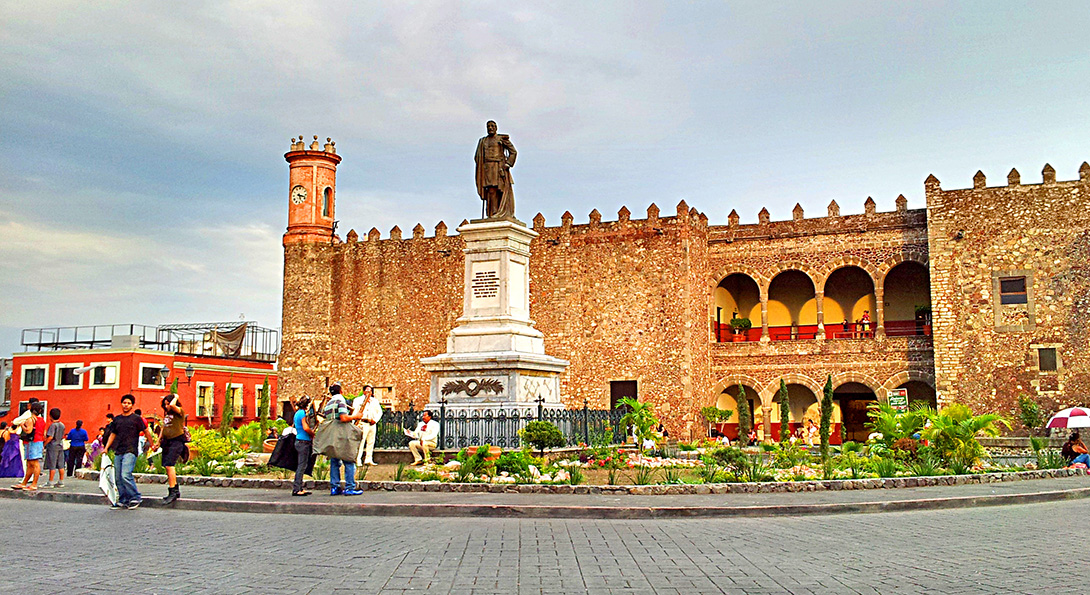 A plaza in Cuernavaca, Mexico, with a large statue standing in the middle of a brick-lined roundabout and people milling around the plaza.