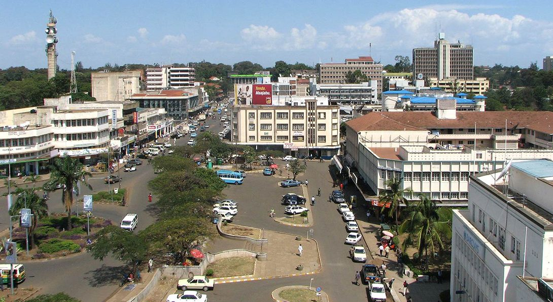 An aerial view of downtown Kisumu, Kenya, with three-story buildings lining a busy street full of cars and people.