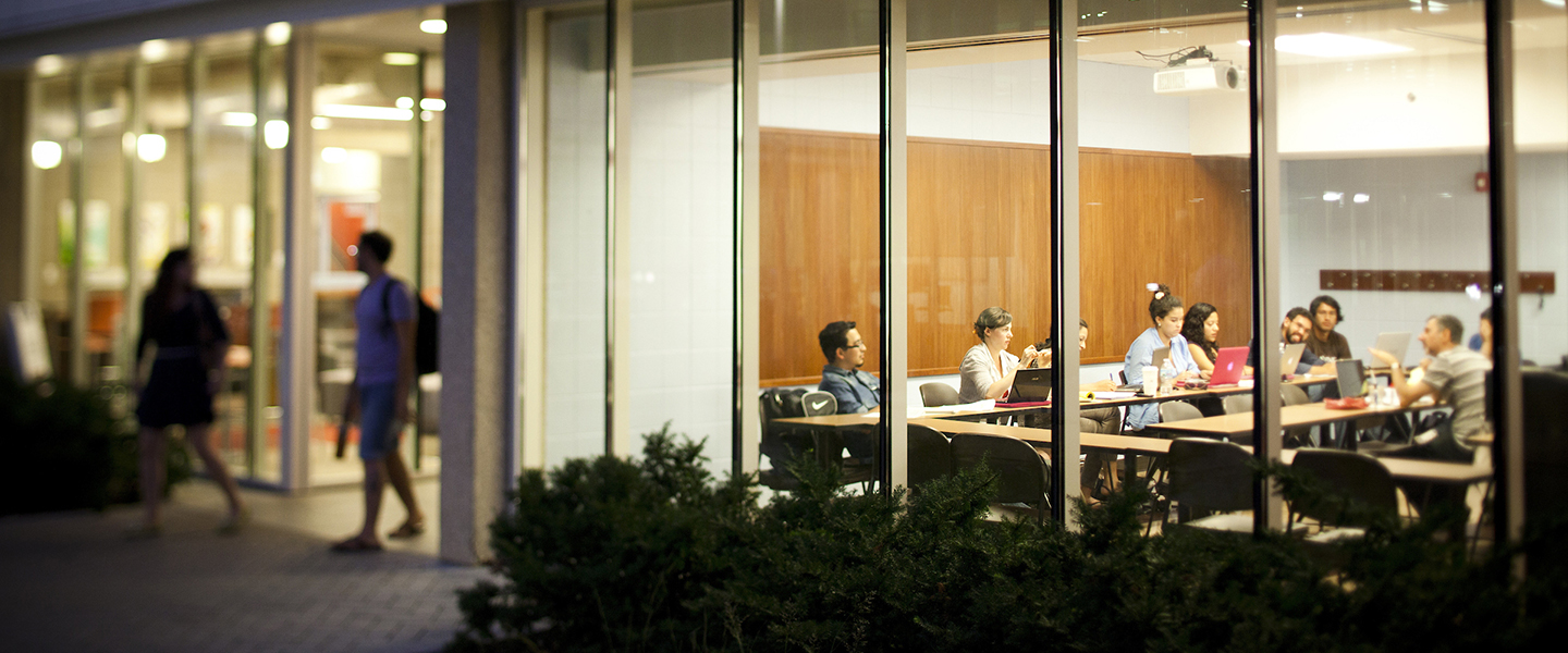 Shown from the outside of a building looking through the windows, students are sitting in a classroom listening to a lecture.  At the left of the image, two students are walking out of the building, which is Douglas Hall on UIC's campus.