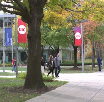 Students walk across sidewalks on UIC's campus on a fall day.