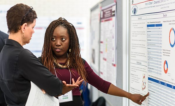 A student gestures toward her poster presentation while discussing her research results with a School of Public Health professor.