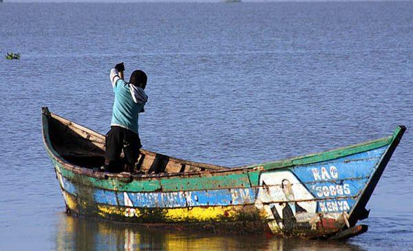 A young boy rows a colorful boat across water near Kisumu, Kenya.