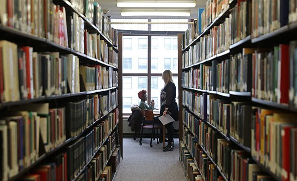 Two students converse sitting at a table near book stacks in a law library.