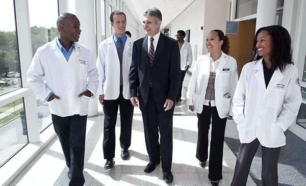 Medical students walk with administrator at UIC's hospital.