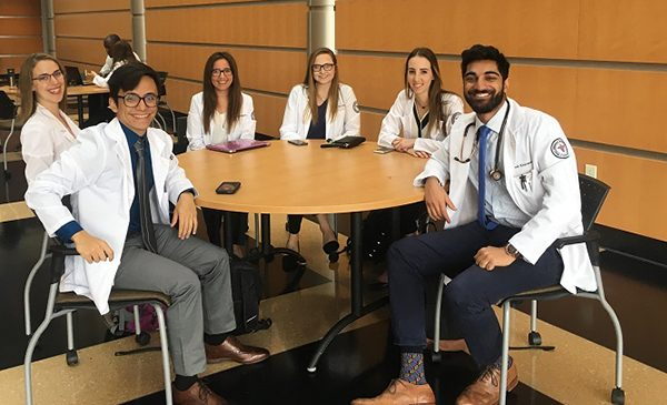 UIC medical students pose for a picture sitting at a round table.