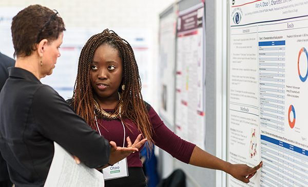 A doctoral student points at her poster presentation while speaking about her research with a faculty member.
