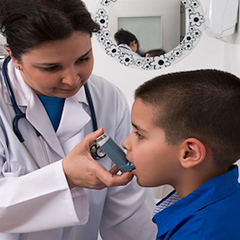 A doctor administers an inhaler to a young boy.