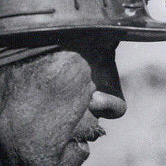 A black and white historical image of a coal miner.