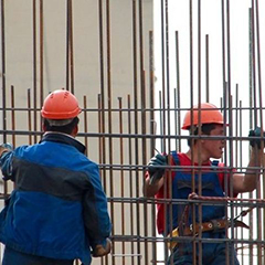 Two workers are assembling rebar atop a large urban building.
