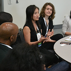 Faculty and students discuss health policy issues sitting around a table at the 2018 American Public Health Association conference.