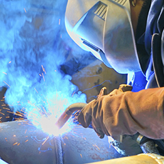 A welder works with a torch melding a piece of metal.