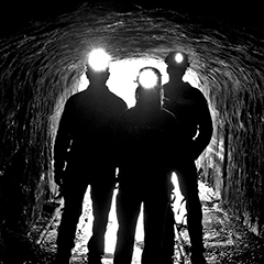 A trio of miners stand in the mouth of a mine entrance, with their headlamps lit.