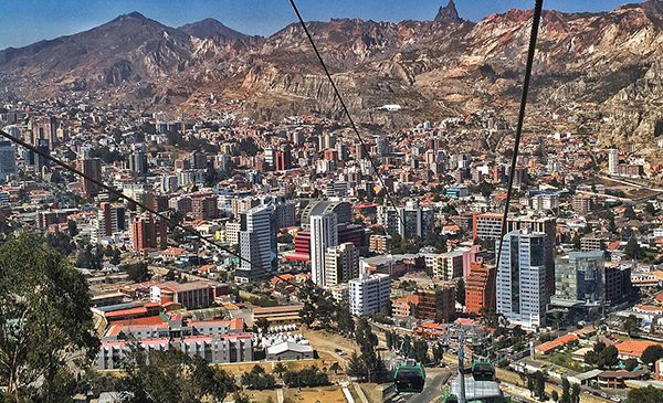La Paz, Bolivia, as viewed from a gondola tower, with tall buildings and homes in a valley and mountains in the background.