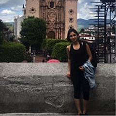 Celina Garza poses for a picture standing on a ledge, with a cathedral in Cuernavaca in the background.