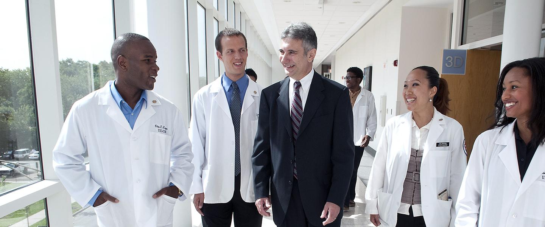 A hospital administrator walks down a hospital hallway with four doctors, having a conversation.