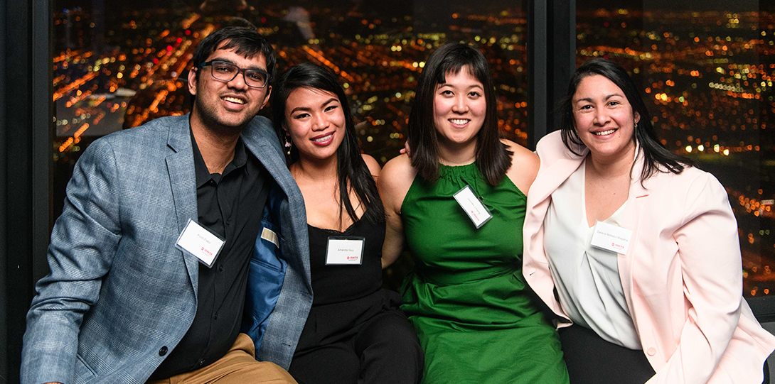 A group of alumni pose for a photo, with the nighttime skyline of Chicago visible through the windows behind them.