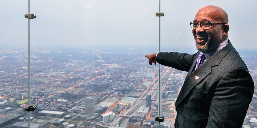 Dean Wayne Giles points through Willis Tower's windows to UIC's campus.