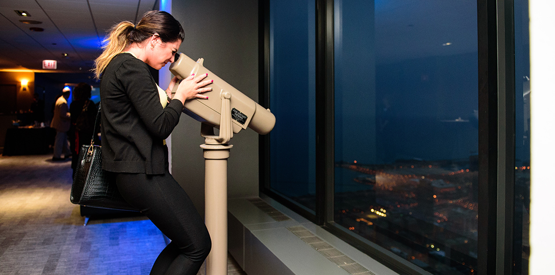An alumna looks through a telescope down towards the city through the windows of Willis Tower.