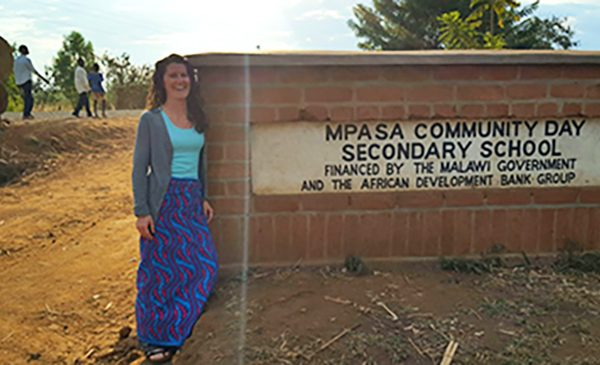 A student poses for a photo next to the sign for the Mpasa Community Secondary School during a global applied practice experience.