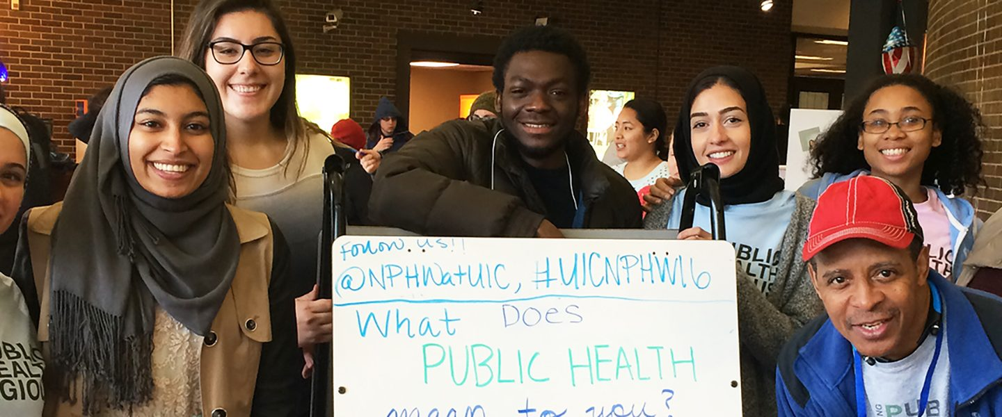 A group of School of Public Health students pose for a photo, with a whiteboard with answers to the question