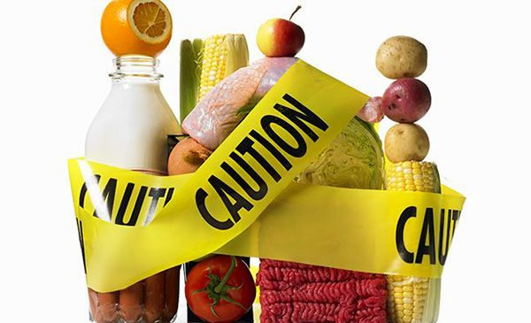 Various food items, including milk bottles, fruits, vegetales, and raw meat are surrounded by caution tape.