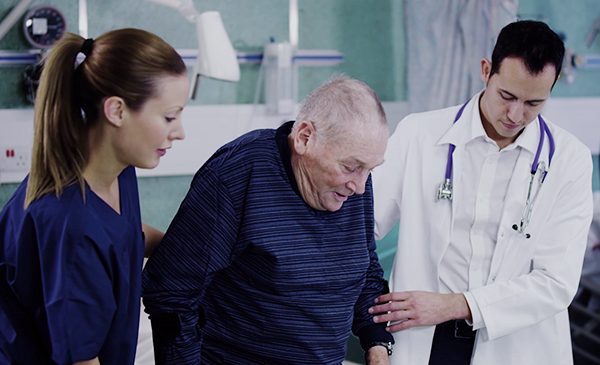 Two doctors walk hand-in-hand with an elderly man in a hospital.