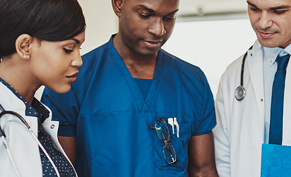 Three doctors examine a medical chart.