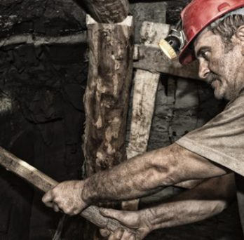 A miner swings a pickax while working in a mine shaft.