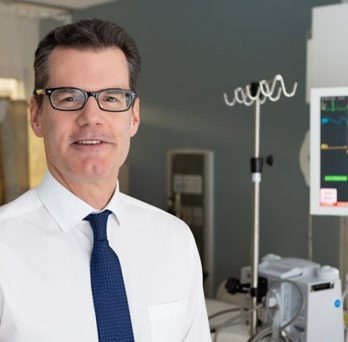 Dr. Stephen Trzeciak poses for a photograph in a hospital room.