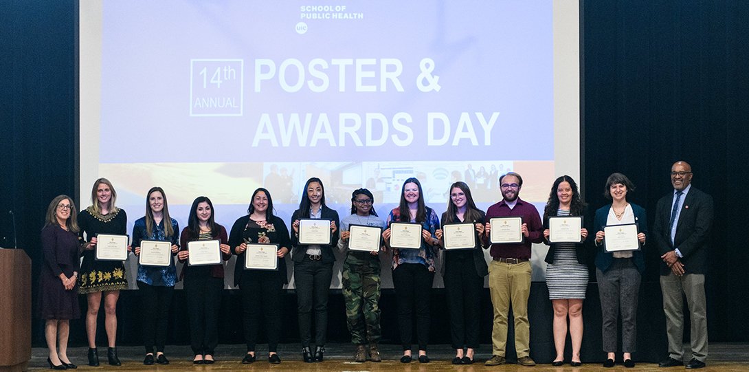 Students pose on a stage with a photo with their research awards.