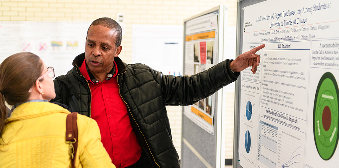 A student points to his poster while explaining his poster to another student.