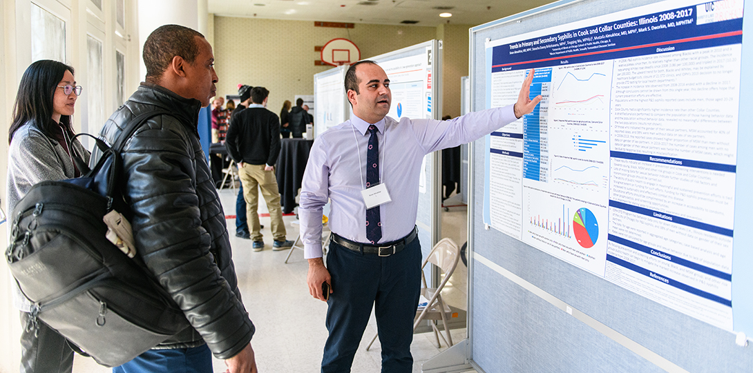 A student gestures toward his research posters while two other students listen to a description of his research.