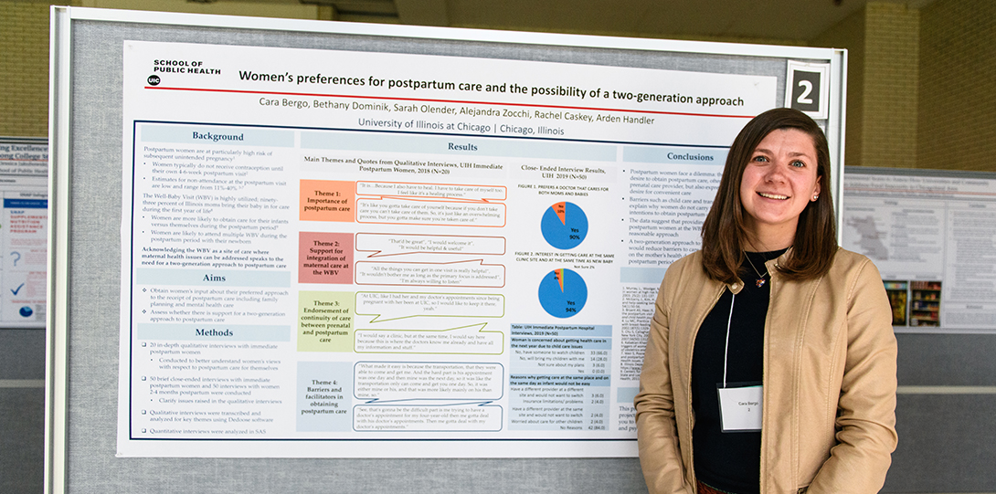 A student poses for a photo standing in front of her research poster.