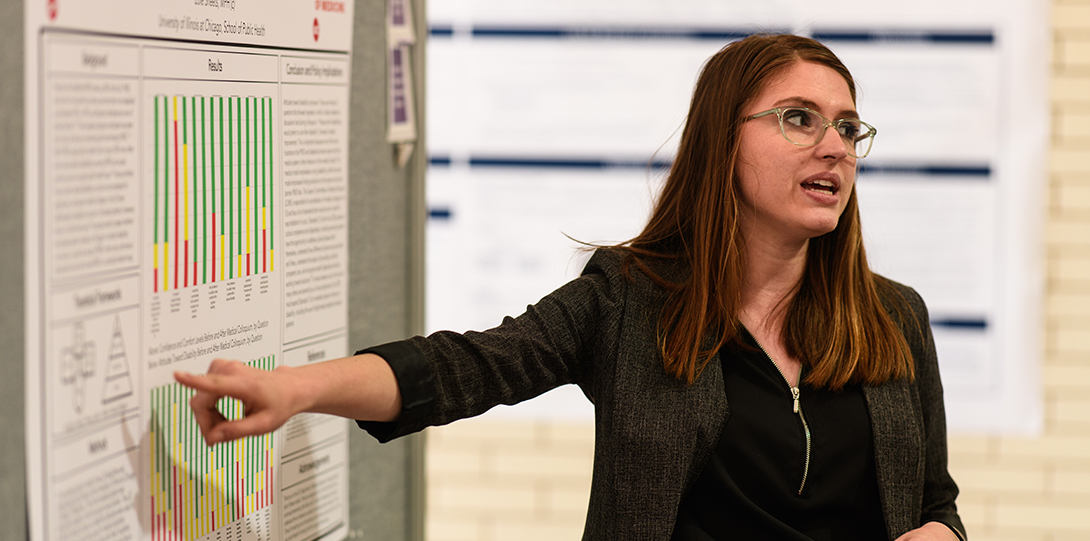 A student points to her poster presentation while explaining her research.