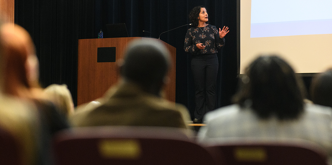 A speaker at the Research Day event stands on a stage in the auditorium, completing her lecture while students are seated in the seats.
