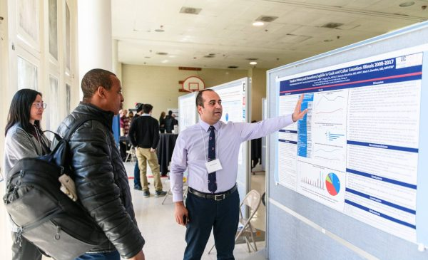 A doctoral student gestures toward his research poster while explaining his research to two fellow students.